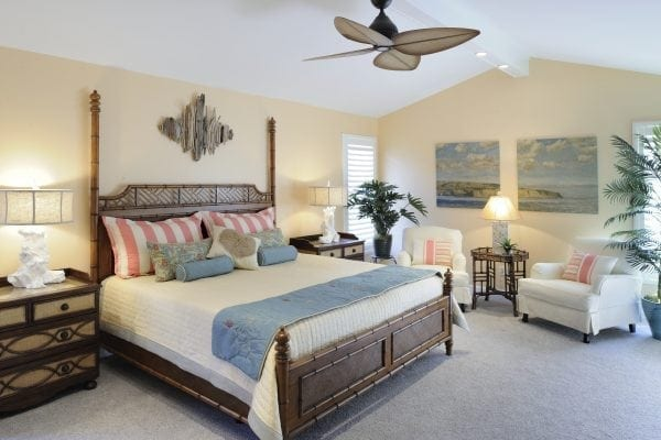 a Tommy Bahama bed takes center stage. Slipcovered chairs are brachy casual.