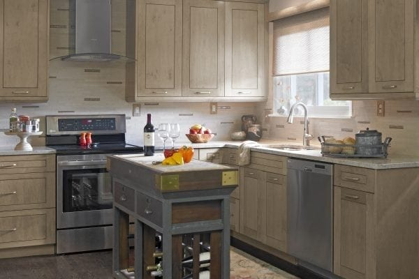 Who says a tiny kitchen needs to be white? Beautifully-grained light wood cabinets anchored by dark hardwoods set the stage for this cozy but infinitely functional kitchen. A free-standing island adds a chopping board and wine storage.