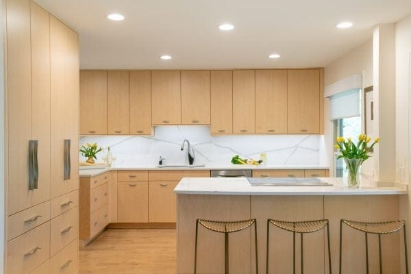 Minimalist look - light wood cabinets with slab doors, same product on the counters and backsplash