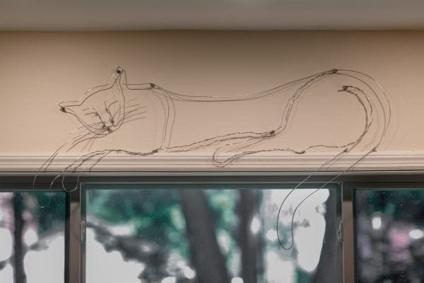 A custom cat sculpture reclines above the kitchen window. He has various objects hanging from his paw at odd times.
