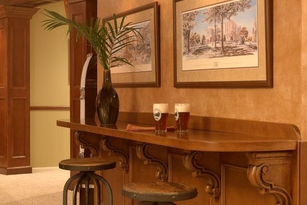 custom wainscoting and bar are reminiscent of an old English pub. Barstools turn for easy TV viewing.