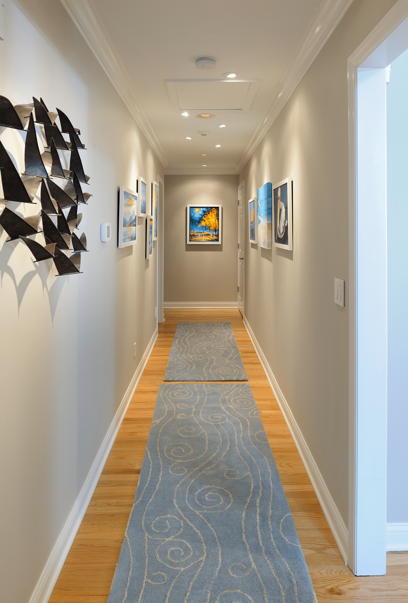 Gray hallway with paintings on walls