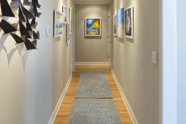 a very long hallway is the perfect spot for a gallery of coastal art, anchored by swirling water on the rugs. Gimbels were added to highlight the art.