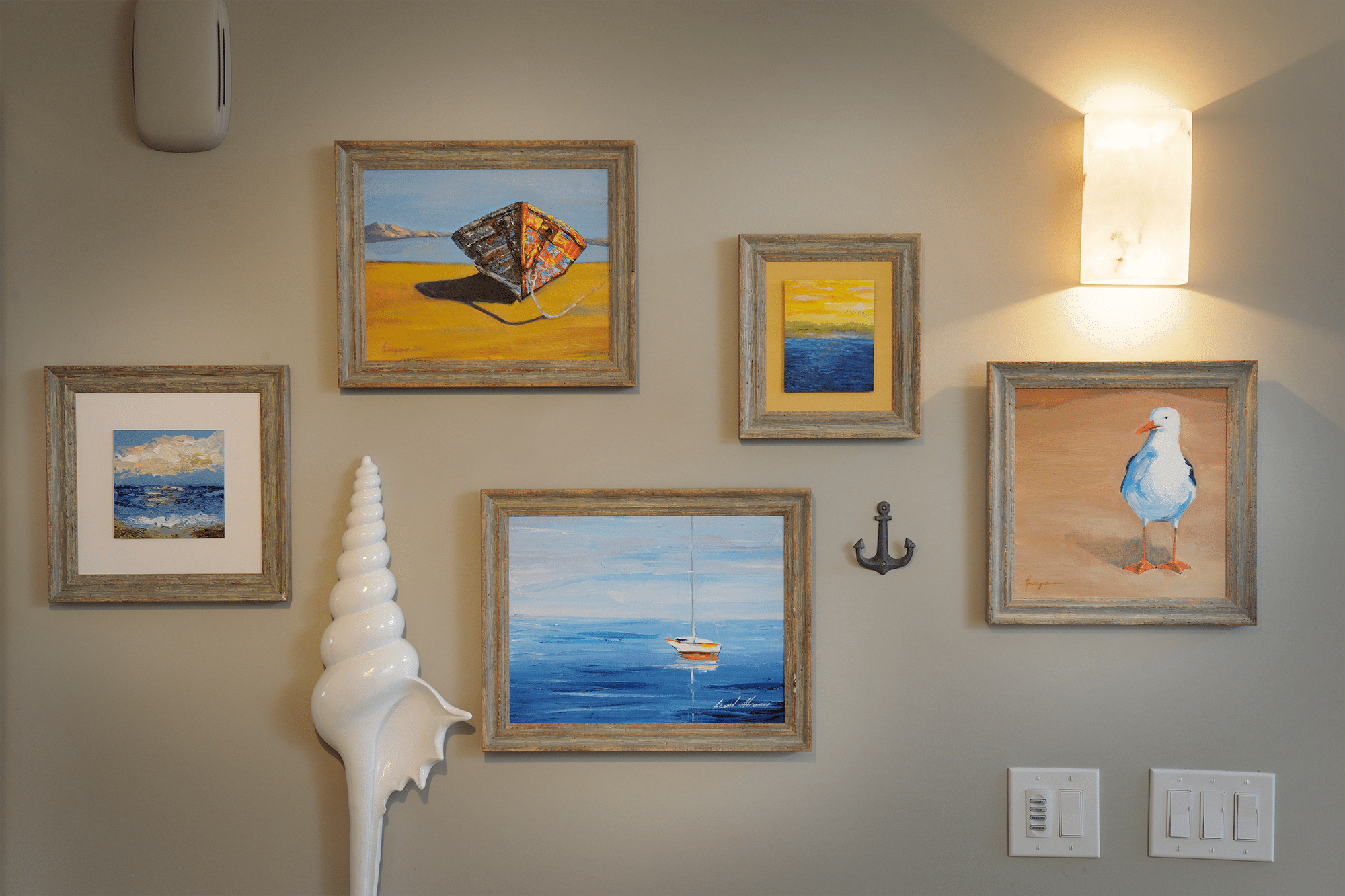 Five rectangular brown wooden framed paintings mounted on wall