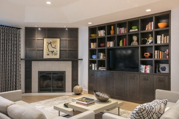 custom bookcase houses TV and artwork. Fireplace surround plays off bookcase squares, for a refined and elegant look. St. Louis Architect and Designer Award, Fireplace Design