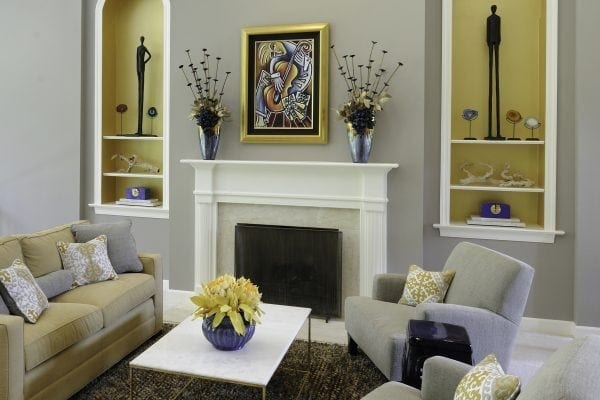 large, awkward openings were painted gold and filled with unique objects. The color palette for the room came from the existing contemporary painting above the fireplace.