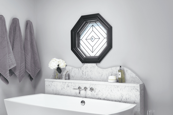 Plumbing shouldn't be inside of an exterior wall; hence the creation of the marble-covered half wall behind the tub which safely houses the plumbing and creates a shelf for bath products.