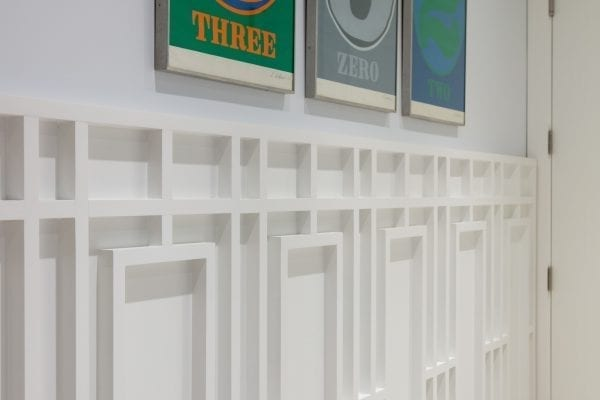 Three assorted-color paintings on white wall
