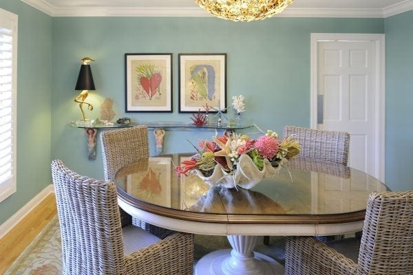 a formal dining room isn't very formal anymore after creating more of a beach patio feel. Custom shell chandelier, rattan chairs, giant clam shell centerpiece.