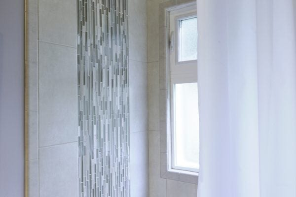 Shower tile and niche closeups – repeating the glass tile mosaic installed vertically gives the illusion of rainfall behind the shower head and on the niche wall. The minimalist tile design is perfect for a contemporary installation.