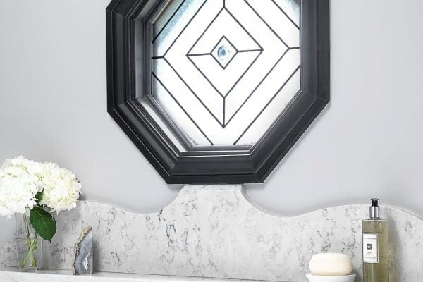 Connecting the hexagon window to the half wall via the artfully designed backsplash kept it from feeling out of place. The shape of the backsplash is repeated as the bottom of the other window's valance. The hexagon window shape is also repeated in the other window's valance.