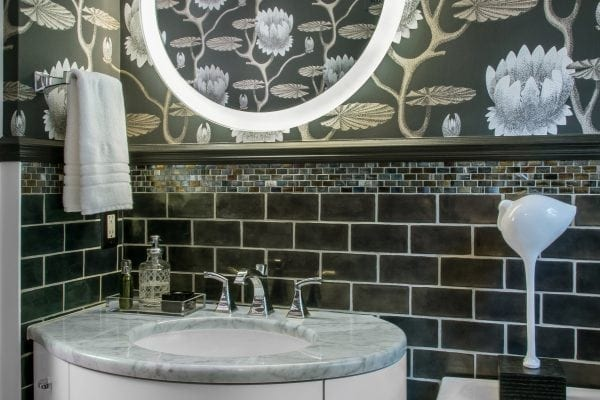 a rounded vanity keeps the space from feeling crowded. The round mirror with edge lighting ended the need for additional sconces that would have cluttered up the wallpaper.