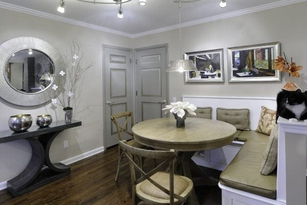 Slab doors were faux-painted to appear as if they have panels. Built-in banquette seating separates the eating space from the living room. The table opens to comfortably seat 8.