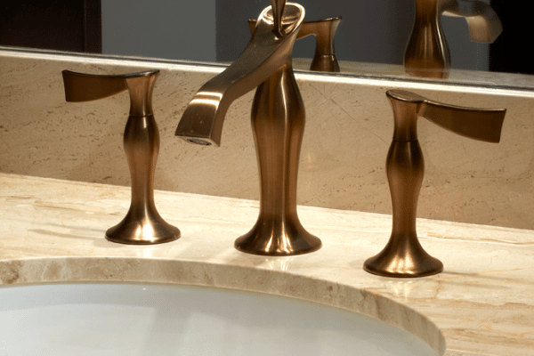 Gold faucet in front of mirror