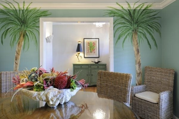 faux-painted palm trees adorn the wall opposite the wave buffet. Front entry has a shell sconce and capiz shell chandelier