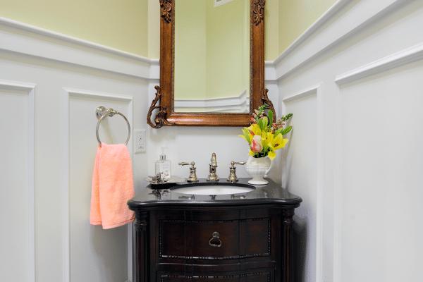 Black 3-drawer chest vanity sink beside mirror
