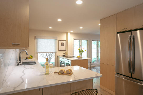 Gray stainless steel French refrigerator with closed door near kitchen island inside well-lit room