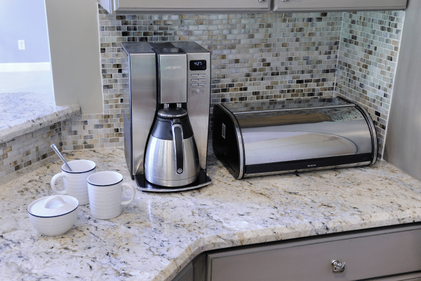 Gray and black coffeemaker on marble top surface beside ceramic mugs