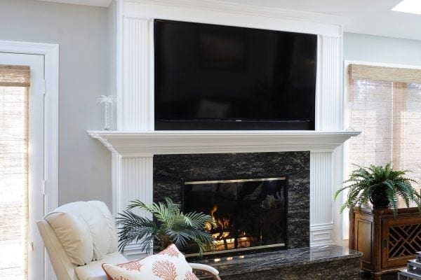 the custom TV surround was created to match the existing wood on each side of the fireplace. The black granite below keeps the TV above from looking like a big black hole.