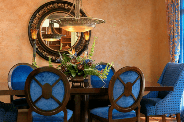 Brown-and-blue wooden table with chairs dining set near mirror on wall
