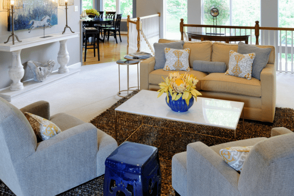Yellow flowers in blue vase centerpiece on white coffee table in the middle of grey sofa set