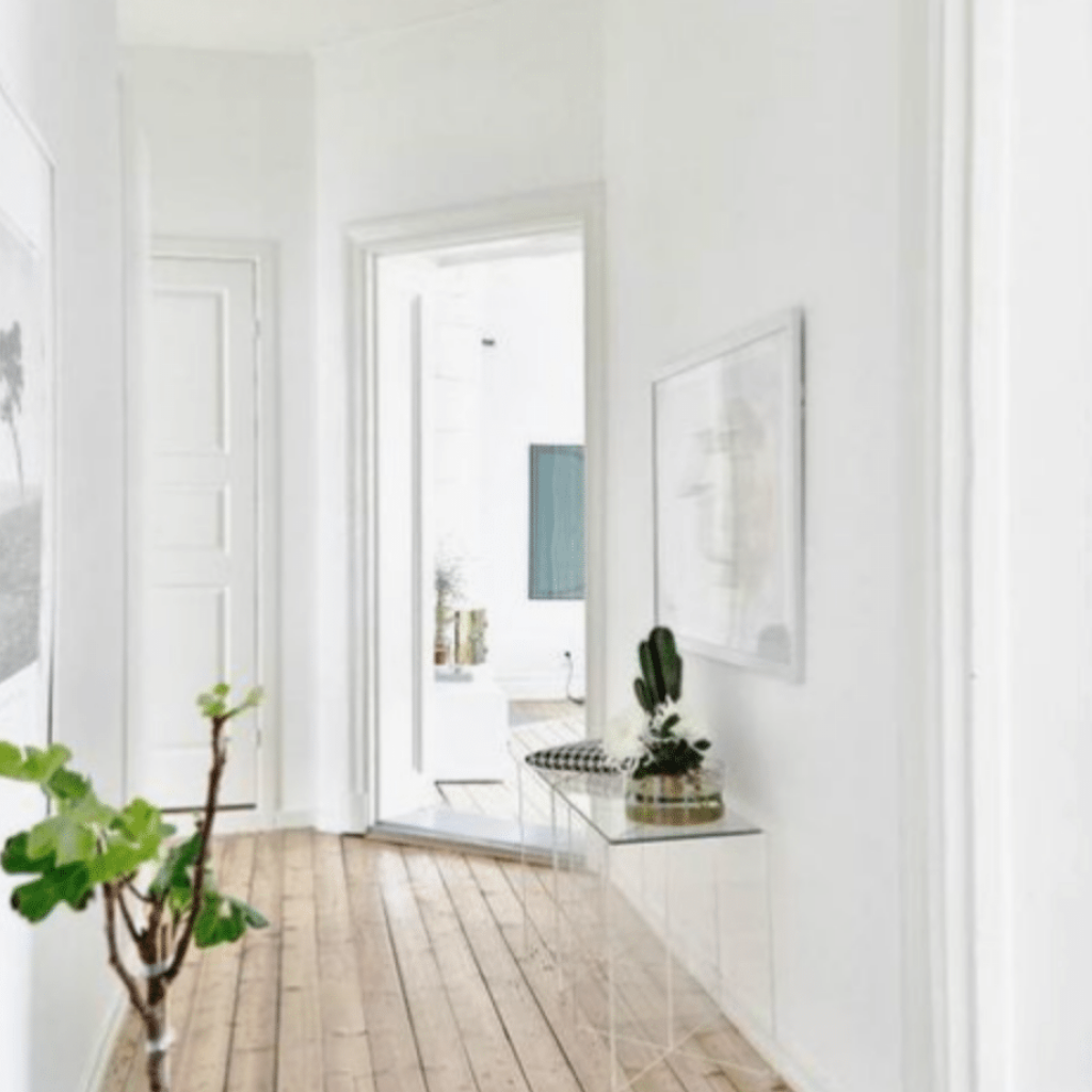 Blonde floors paired with crisp white walls creates a very Scandinavian look in a space that is swimming in sunshine for a relaxed summery vibe.