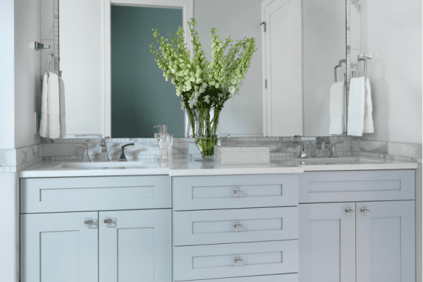 Green and white flower centerpiece placed on white wooden vanity combo