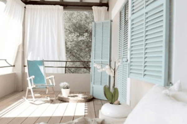 White sofa on wooden deck beside window