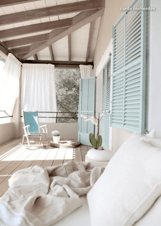 White sofa on wooden deck beside window