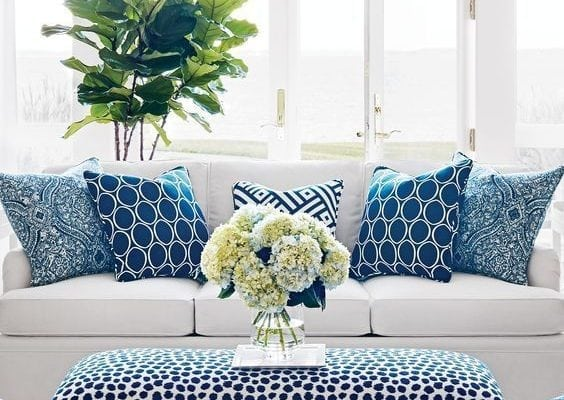 White-and-green petaled flower centerpiece on rectangular blue and white fabric padded ottoman bench