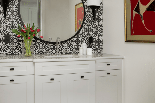 Taking the striking black and white patterned tile up on the wall was a bold design choice that made all the difference in this special powder room.
