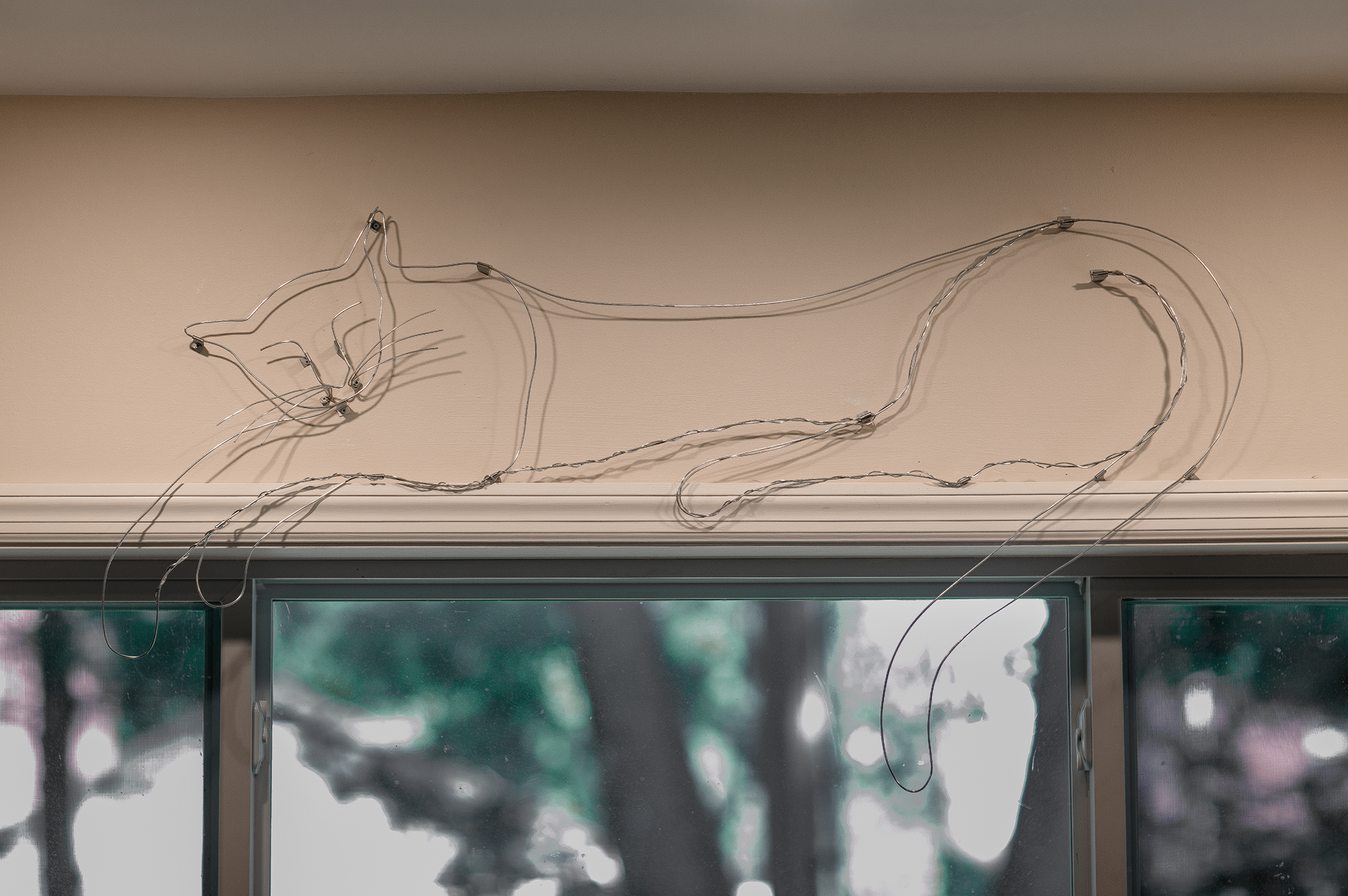 wire cat resting above a door