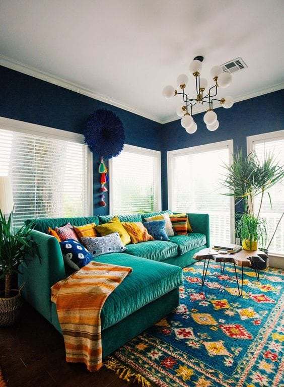 Teal sectional couch near blinded windows