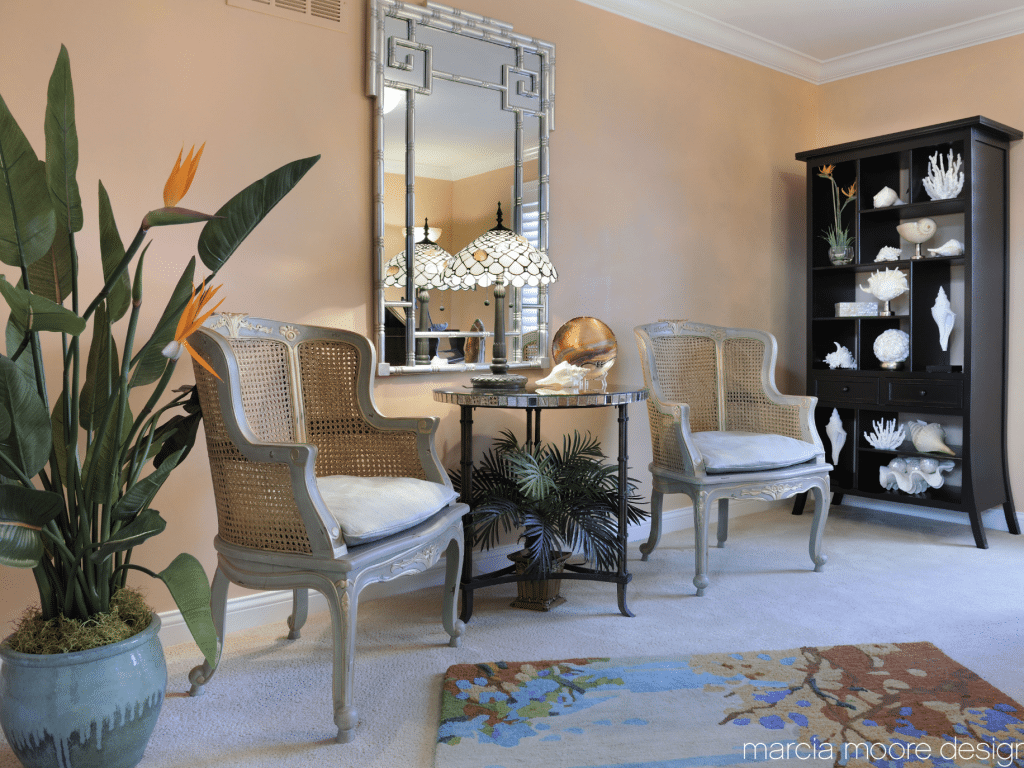 Two beige wooden armchairs placed near wall with mirror