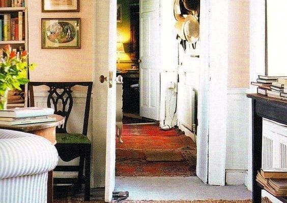 Black wooden chair beside wall near area rug