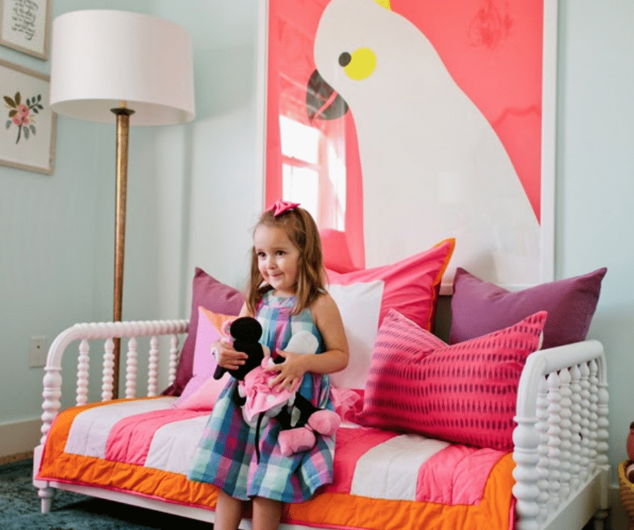 Girl holding Minnie Mouse plush toy on whtie bed