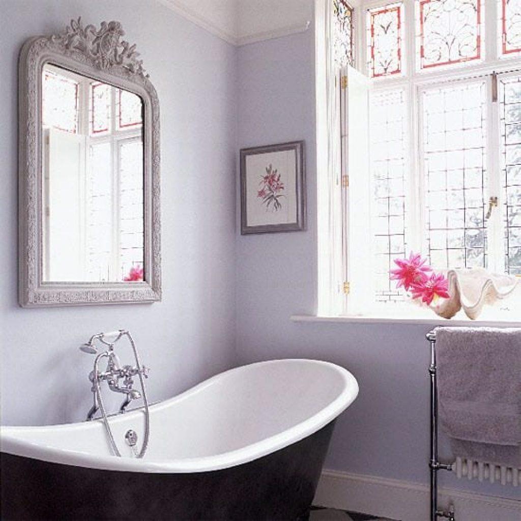 Black and white bathtub near gray framed wall mirror near closed window