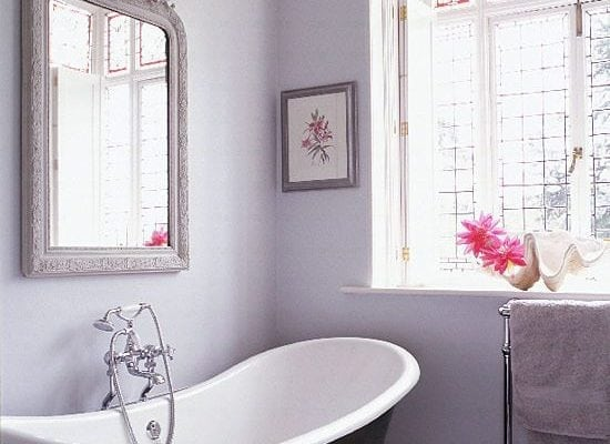 Black and white bathtub near gray framed wall mirror near closed window