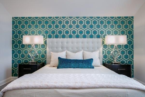 Three white throw pillows on white bedspread