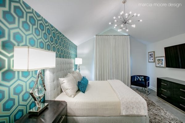 Turned-on silver table lamp beside white bed frame