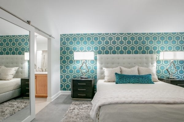 White bed with tufted headboard near door