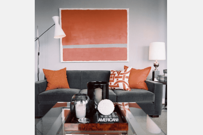 grey couch with orange pillows