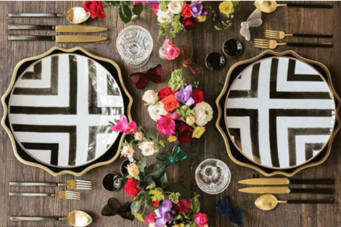 black and white plates with gold silverware