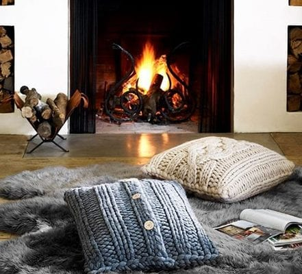 pillows and fur rub on floor in front of fireplace