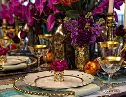 gold table setting with purple flowers