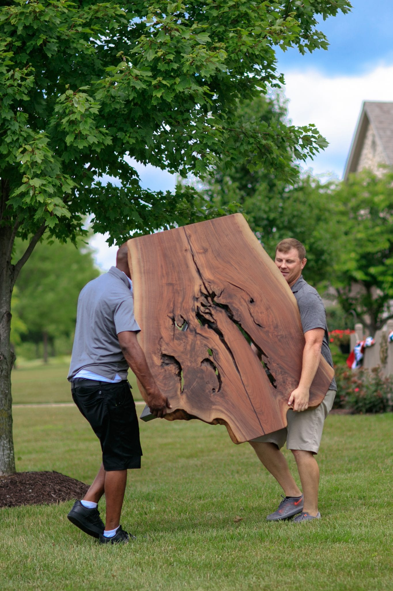 two men carrying a large wooden table