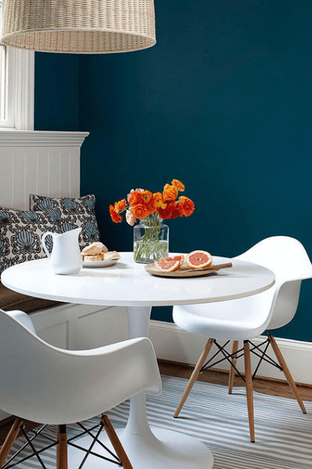 white table and chairs near a blue wall